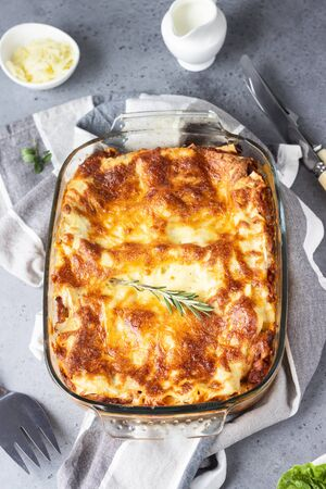 Traditional Italian lasagna with minced meat, tomato and cheese. Light gray concrete background, selective focus.
