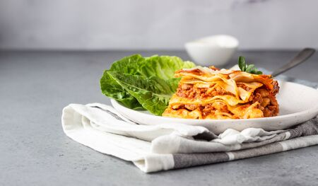 Portion of traditional Italian lasagna with minced meat, tomato and cheese served with green salad on a plate. Light gray concrete background, selective focus.