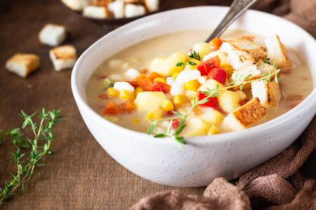 Bowl of homemade corn chowder soup with potatoes, carrots, red bell pepper and croutons in a wooden tray. Delicious cozy first course, comfort food.