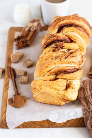 Cinnamon babka or swirl brioche bread. Cinnamon roll bread. Povitica: traditional Polish sweet bread. Homemade pastry for breakfast. Light gray background.
