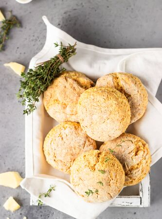 Freshly baked delicious homemade English scones with cheese and thyme on a light gray wooden tray. Gray stone background. Archivio Fotografico