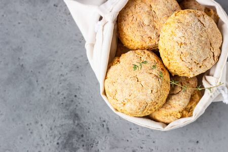 Canvas bag with homemade scone with cheese, thyme and pieces of cheese. Freshly baked delicious English scones. Gray stone background.