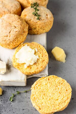 Wooden cutting board with delicious English scones with cheese. Perfect breakfast or lunch. Gray stone background. Imagens
