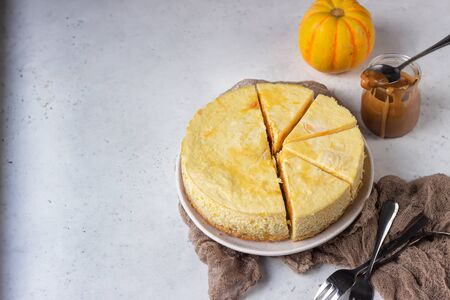 Pumpkin cheesecake with caramel sauce, light gray stone background. Selective focus. Stock Photo