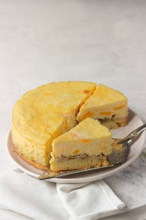 Pumpkin cheesecake with caramel sauce, light gray stone background. Selective focus.