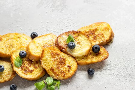 Torrijas, typical Spanish sweet fried toasts with blueberries, coconut flakes and mint on a light gray stone background. Traditional dessert for Lent and Easter.