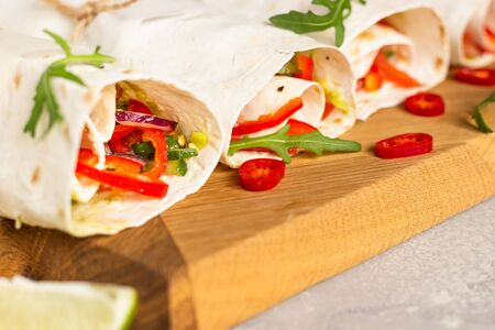 Fresh vegan tortilla wraps with bell pepper, tomato and cucumber on wooden cutting board with lime and chili pepper. Light gray stone background.
