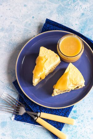 Plate with two pieces of pumpkin cheesecake and with caramel topping on a blue ceramic plate, light blue stone background. Selective focus.