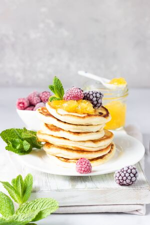 Homemade pancakes with jam, frozen raspberries and blackberries and mint on wooden cutting board. Light gray background. Breakfast Stock Photo