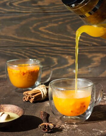Process brewing tea, hot colorful sea buckthorn tea is poured into a glass cup.
