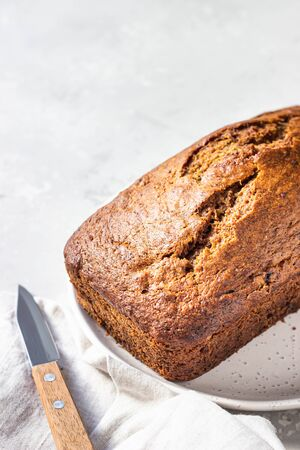 Sugar-free banana bread on a ceramic plate, light concrete background. Morning atmospheric lighting, trendy soft shadows, selective focus. Copy space. Imagens