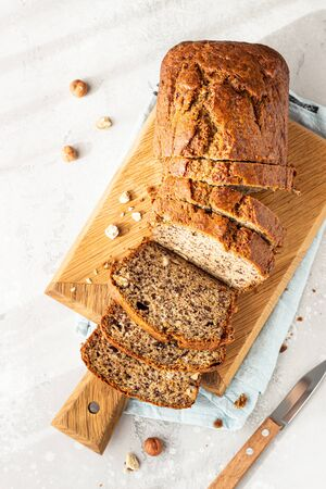 Homemade banana bread or cake with hazelnut on wooden cutting board, light stone background. Trendy soft shadows, atmospheric lighting, selective focus.