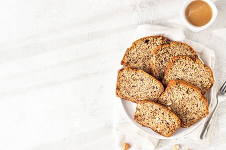 Sliced banana hazelnut bread on a ceramic plate with a cup of coffee. Morning atmospheric lighting, trendy soft shadows, selective focus. Idea for healthy diet breakfast. Imagens