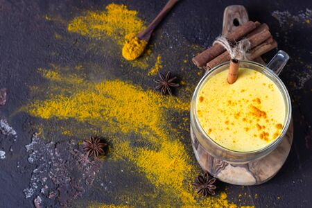 Golden milk or latte with turmeric (curcuma) powder with spices, dark brown concrete background. Trendy detox, immune boosting, anti-inflammatory healthy cozy drink.