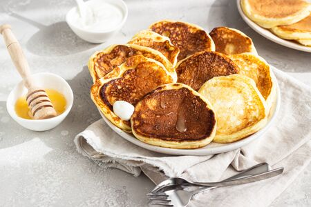 Homemade pancakes with honey and sour cream, sunny shadowed table surface. Light gray concrete background. Natural light and shadows food photography concept. Breakfast Standard-Bild