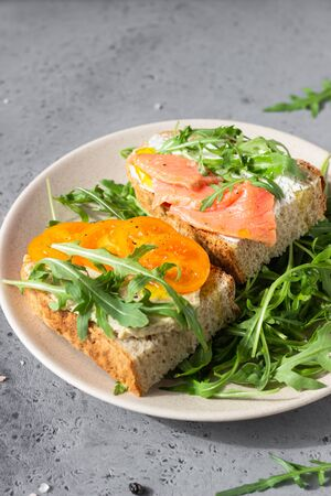 Healthy open sandwiches with artisan bread with cream cheese, salmon, tomatoes and arugula on ceramic plate. Balanced diet concept.