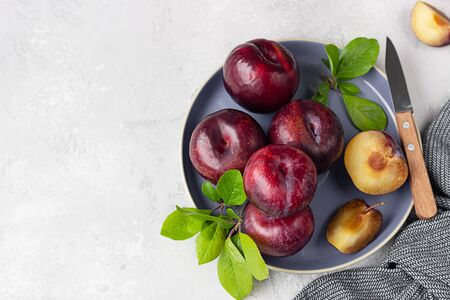 Whole purple plums and slices with leaves and knife on ceramic plate, light grey concrete background.