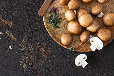 Fresh champignon on a wooden plate, dark brown texture background. Brown mushrooms.
