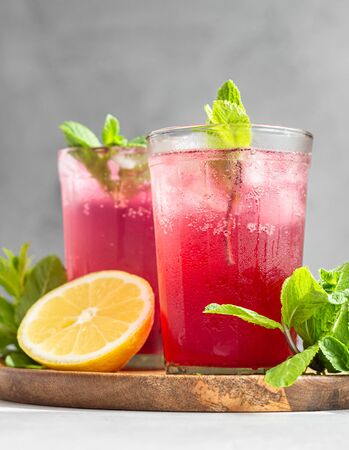 Cold sparkling hibiscus tea with lemon, mint and ice in glasses on a grey stone background. Summer drink, lemonade.