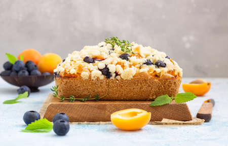 Blueberry and apricot crumble cake decorated with thyme on wooden cutting board. Blue background. Reklamní fotografie - 150601872