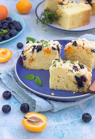 Slices of apricot and blueberry crumble cake on blue ceramic plate decorated with thyme. Blue background.