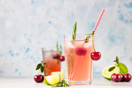 Cocktail or lemonade with cherries, lime and rosemary on a gray table. Summer refreshment drink.