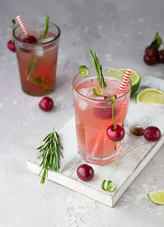 Cold pink non-alcohol cocktail with cherries, lime and rosemary on light wooden board, gray concrete background.
