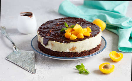 Cream mousse cake or no baked cheesecake with apricot decorated with chocolate, fresh apricots and mint on light background.