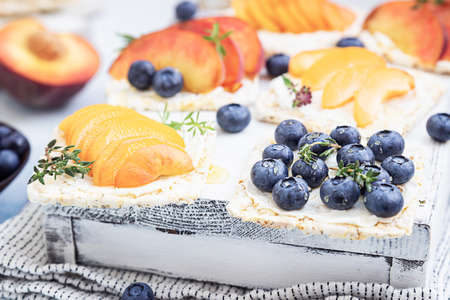 Mini sandwiches with cream cheese, fruits and berries. Healthy toasts with cream cheese, blueberries, apricots, nectarines and honey on a light blue background.