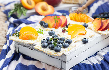 Healthy picnic for a summer vacation on the sea beach with fresh fruits and berries, sandwiches with cream cheese, fruits and blueberries with honey on a blue and white cloth. Archivio Fotografico