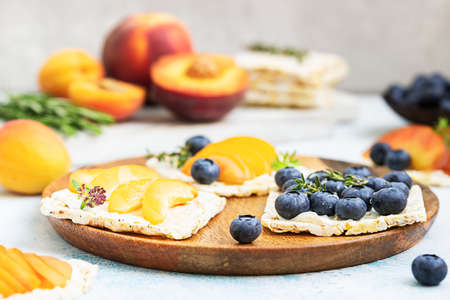 Mini rice cakes with blueberries, apricots, nectarines and cream cheese with honey for healthy breakfast. Light blue background. Summer dieting sandwiches. Archivio Fotografico
