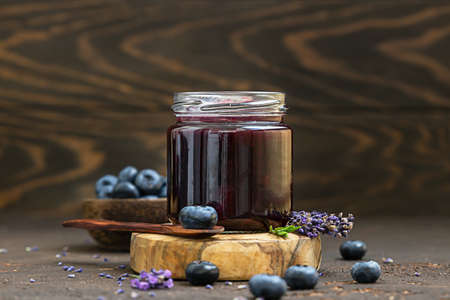 Glass jar and spoon with delicious blueberry jam with fresh berries, lavender and rosemary on brown table. Healthy food for breakfast. Archivio Fotografico
