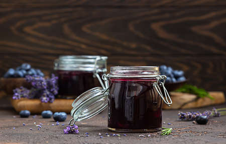 Composition with sweet blueberries jam with fresh berries, lavender and rosemary on brown concrete background. Summer harvest concept.