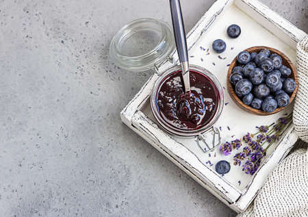 Homemade blueberry jam with fresh blueberries and lavender. Marmalade on spoon and jar. Gray concrete background. Archivio Fotografico
