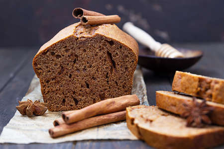 Gingerbread and honey loaf cake with cinnamon and anise on old wooden background. Rustic style.