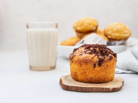 Vanilla muffins and muffins with streusel in paper cups with a glass of milk on light background. Breakfast or snack for children.