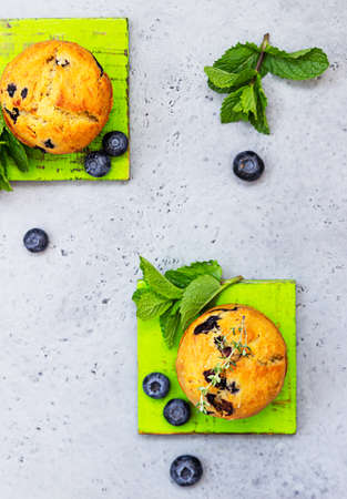 Fresh homemade delicious blueberry muffins decorated with thyme, fresh berries and mint on grey background.