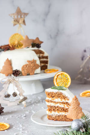 Christmas or New Year gingerbread cake with white cream decorated with gingerbread cookies, fir tree branches, cones, spices and dried orange slice. Winter cake. Gray concrete background.