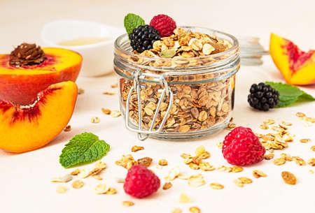 Homemade crunchy granola in glass jar, peaches, berries, honey and mint, light concrete background. Healthy vegan or vegetarian snack. Selective focus. Фото со стока