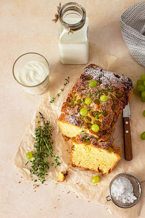 Delicious homemade grape loaf cake with thyme and sugar powder on parchment paper. Light stone background.