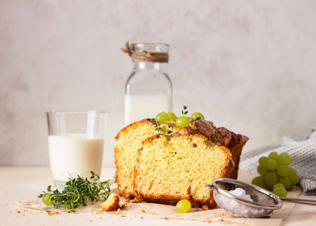 Delicious homemade grape loaf cake with thyme and sugar powder on parchment paper. Light background. Stock fotó