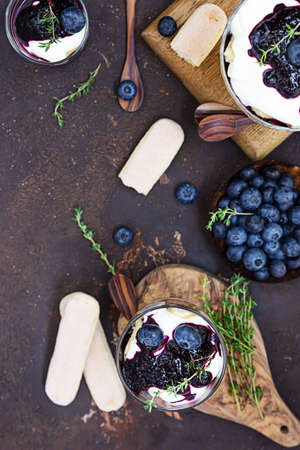 Dessert from mascarpone or ricotta cheese, blueberries and biscuit in glass on a dark concrete background. No baked cheesecake or tiramisu. Zdjęcie Seryjne