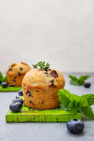 Fresh homemade delicious blueberry muffins decorated with thyme, fresh berries and mint on gray background.