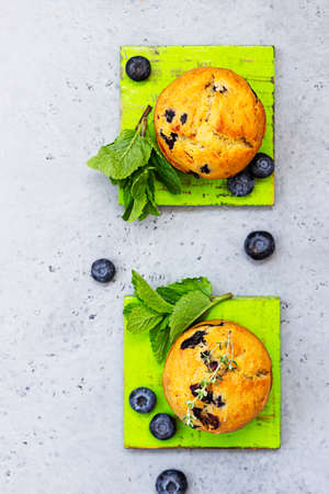 Fresh homemade delicious blueberry muffins decorated with thyme, fresh berries and mint on gray concrete background.