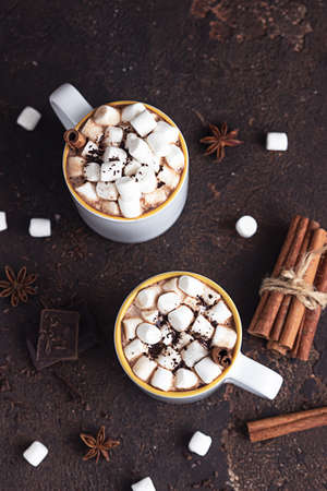 Two white ceramic cups with hot cocoa or chocolate with marshmallow and anise, cinnamon and bitter chocolate on dark stone background. 스톡 콘텐츠