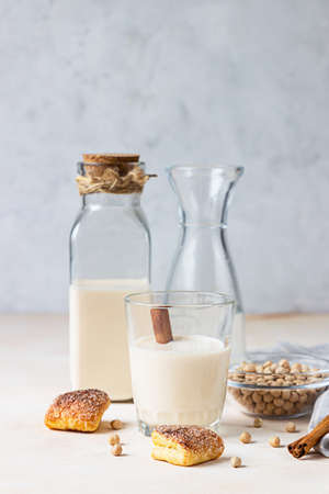 Chickpea vegetarian milk in a bottle and glass and raw chickpeas on light background. Lactose free non dairy products. Healthy vegan food concept.