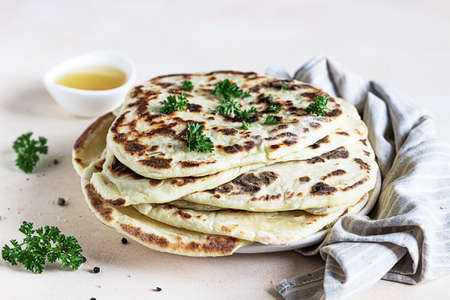 Indian homemade traditional flatbread with parsley and olive oil. Chapati, roti or naan Indian crispy flatbread.