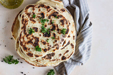 Indian homemade traditional flatbread with fresh parsley and olive oil. Chapati, roti or naan Indian crispy flatbread.