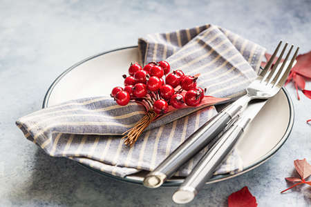Autumn table setting. Red autumn leaves, red decorative berries, fork and knife on blue concrete background.