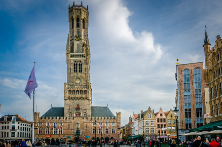 Market Square (Markt) Provincial government in Bruges, Belgium. View to Belfort tower building in historical centre of old town day panorama with blue sky and clouds. Editorial
